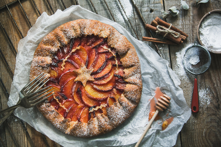 Galette with peaches on the old wooden background. Beautiful sweet cake background