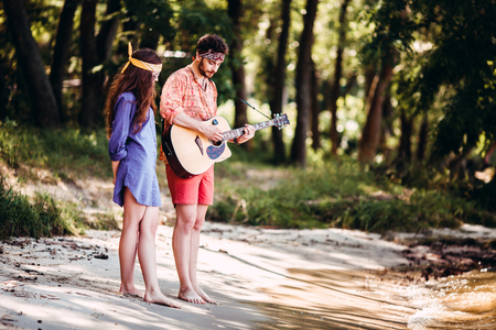 Beautiful young couple in love in hippie style with the guitar resting on the beach in summer. Man playing guitar to his girlfriend
