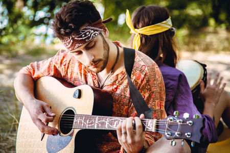 Beautiful young couple in love in hippie style rest on the nature. A man plays the guitar and the girl plays the drum