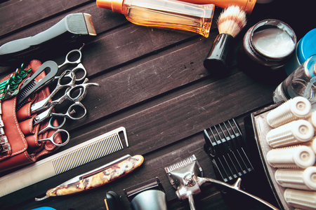 Beautiful professional tools professional Barber kits, scissors, a sharp razor, mechanical and electronic hair clippers, hair curlers, clips. Vintage stylish background for beauty salon with free space