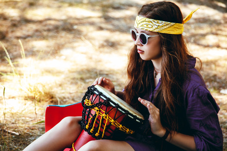 Beautiful young girl in hippie style outdoors sitting on the grass in sunglasses drumming his hands on the drum