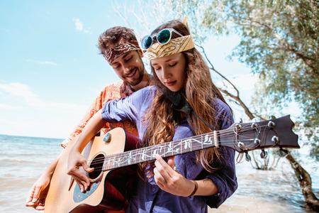 Beautiful young couple in love in hippie style with the guitar resting on the beach in summer. A Girl holding a guitar, man teaches how to play his girlfriend on the seafront
