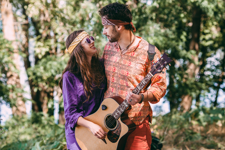 Beautiful young couple in love in hippie style with the guitar resting on the beach in summer. A man and a girl are hugging and smiling