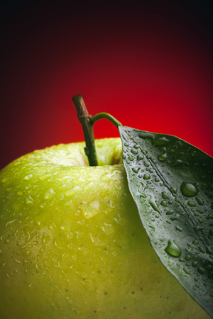 Large beautiful green apple with a leaf and water drops on a red background Stock Photo