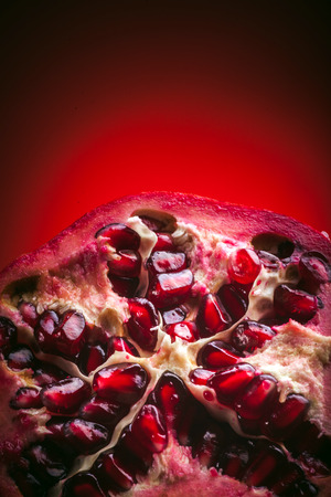 Background made of red pomegranate seeds. Half of the beautiful ripe fruit pomegranate. Top view. Фото со стока