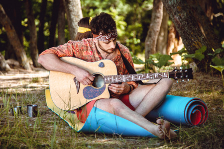 A young, unshaven male hippie outdoors sitting on the grass and plays the guitar behind his girlfriend sits and listens Stock Photo