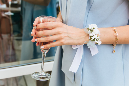 bride in dress with a boutonniere holds a glass of champagne Stock Photo