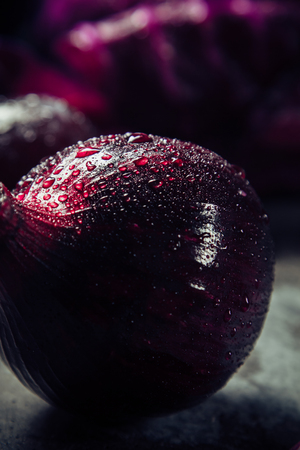 Beautiful purple bow with dew drops on the background of other vegetables Stock Photo