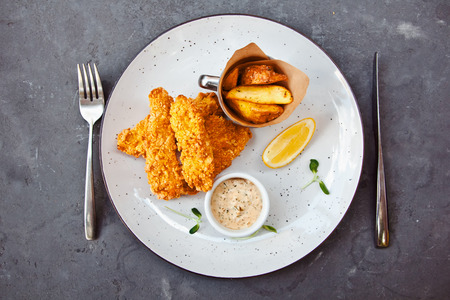 Fish and chips on a white plate with fork and knife on dark background