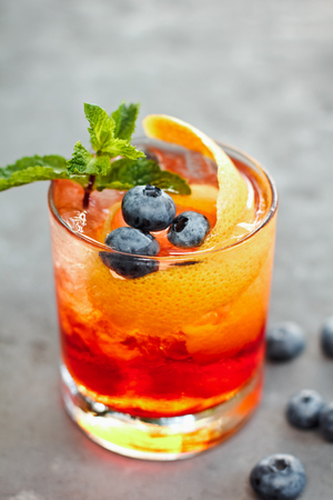 Closeup glass of iced  Berry Soda, with fruit syrup topped with sliced fresh orange and blueberry on table, Summer Cocktail Stock Photo