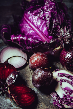 Beautiful dark background with fruits and vegetables of one color: blue cabbage, beets, onions, Basil, plum