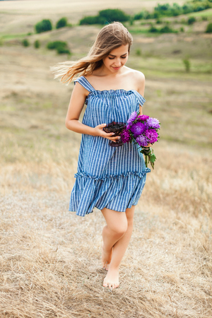 Girl in blue summer dress outdoors in the countryside carries a bouquet of flowers in his hands