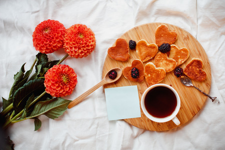 A homemade Breakfast or late Breakfast: American pancakes in the shape of a heart style, served with berries, blackberries and a Cup of black tea with a bouquet of flowers