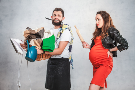 A beautiful pregnant woman with a big belly in a red dress with a rolling pin in her hands grimacing at her husband who holds a basket with clothes, iron and watering pad. Couple in love, family life, values, character, leader Stock Photo