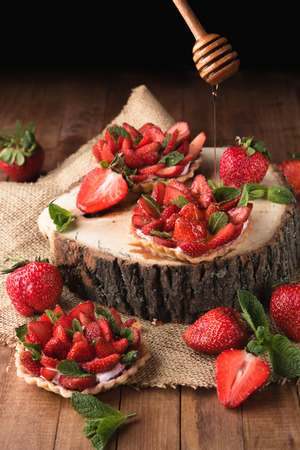 Beautiful basket cake with fresh strawberries and honey on wooden background Imagens
