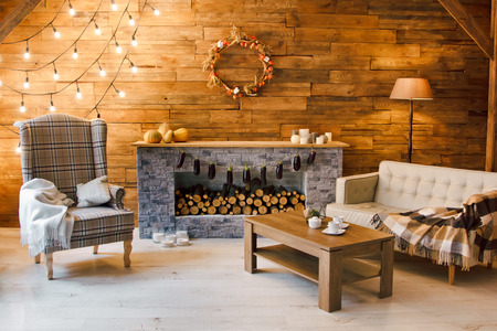 Home comfort. Armchair near the fireplace with firewood. Photo of interior of room with a wooden wall, wreath and garlands, Christmas atmosphere Archivio Fotografico