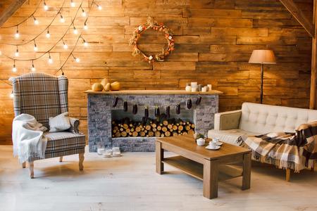 Confort en el hogar. Sillón cerca de la chimenea con leña. Foto del interior de la habitación con una pared de madera, corona y guirnaldas, ambiente navideño