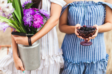 Girls in summer dresses on the nature: one in the hands of a bouquet of flowers, and the second BlackBerry