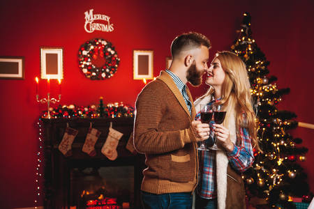 Attractive happy couple on Christmas day standing in front of the decorated tree smiling lovingly into each others eyes and holding glasses with red wine