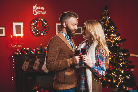 Aantrekkelijk gelukkig paar op eerste kerstdag staan ??ten overstaan ??van de versierde boom lachende liefdevol in elkaars ogen en bedrijf bril met rode wijn Stockfoto