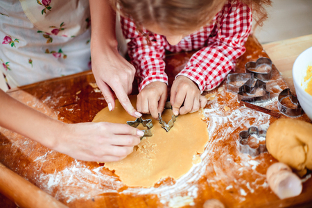 Merry Christmas and Happy Holidays. Family preparation holiday food. Mother and daughter cooking cookies in New Year interior with Christmas tree. Standard-Bild