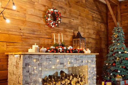 Photo de l'intérieur de la pièce avec un mur en bois, une guirlande et des guirlandes, un arbre de Noël, une cheminée avec du bois de chauffage. Ambiance de Noël Confort de la maison Banque d'images - 88168336