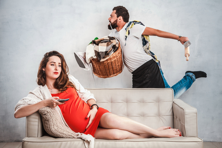 Pregnant woman with big tummies is sitting on the couch and watching TV, and the husband with a frightened gaze is holding a basket with clothes, an iron and a watering pad. Character, leader