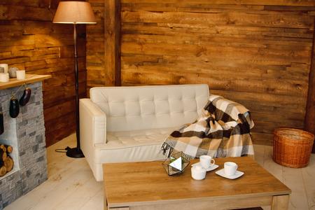 自宅の快適さ。薪を暖炉のそばの肘掛け椅子。木製の壁、花輪、花輪、クリスマスの雰囲気で部屋のインテリアの写真 写真素材