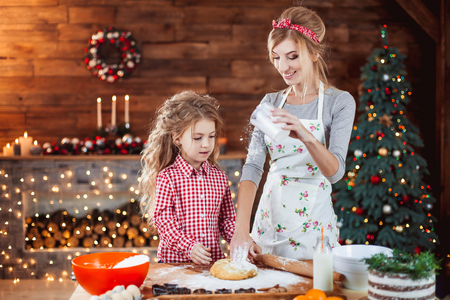Merry Christmas and Happy Holidays. Family preparation holiday food. Mother and daughter cooking cookies in New Year interior with Christmas tree. Imagens