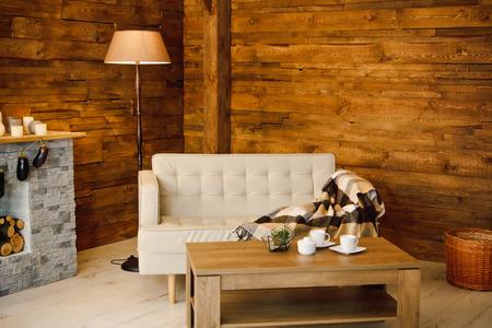 Thuiscomfort. Leunstoel bij de open haard met brandhout. Foto van interieur van kamer met houten muur, krans en kransen, kerst sfeer