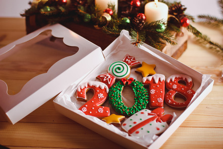 Christmas homemade gingerbread cookies 2018 in gift box on wooden table with oranges Foto de archivo