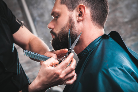 Handsome bearded man having his beard cut by hairdresser at the barbershop. A professional job with a dangerous razor, salon Stock Photo