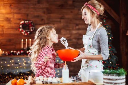 Merry Christmas and Happy Holidays. Family preparation holiday food. Mother and daughter cooking cookies in New Year interior with Christmas tree. Archivio Fotografico