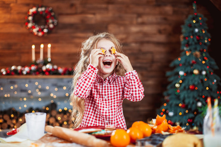Happy little child, cute kid girl at the table in domestic kitchen making gingerbread xmas cookies decorated for Christmas holiday. Girl helping and having fun