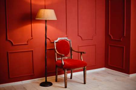 A beautiful luxurious interior of the room with an armchair and a glowing lamp against a red wall. Christmas
