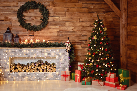 Foto van het interieur van de kamer met een houten muur, krans en slingers, kerstboom, open haard met brandhout. Kerstsfeer. Thuis comfort