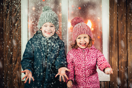 On Christmas night an adorable little boy  with his sister a girl laugh near the window the snow falls. They are waiting for Santa Claus.