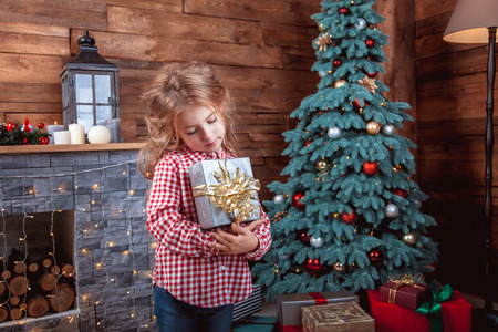 Adorable little baby girl with gift in hand in the New Year room with a Christmas tree. The concept of a happy childhood, magic, family Reklamní fotografie