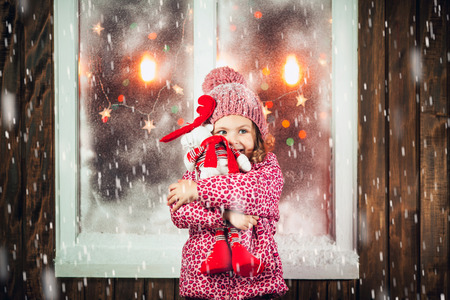 On Christmas night an adorable little girl near the window the snow falls. Фото со стока