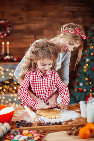 Merry Christmas and Happy Holidays. Family preparation holiday food. Mother and daughter cooking cookies in New Year interior with Christmas tree. Фото со стока