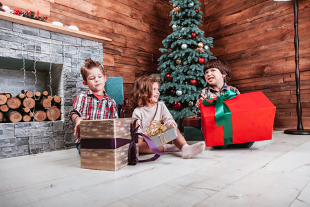Beautiful children playing with gifts in hand in a Christmas interior with Christmas tree and fireplace. The concept of a family holiday