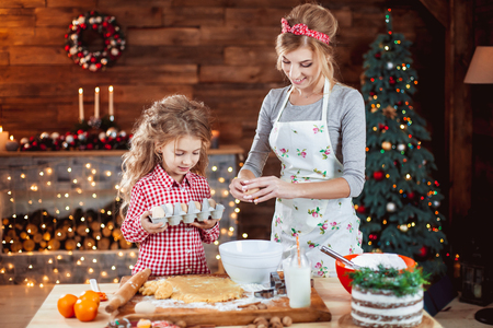 Merry Christmas and Happy Holidays. Family preparation holiday food. Mother and daughter cooking cookies in New Year interior with Christmas tree. Reklamní fotografie