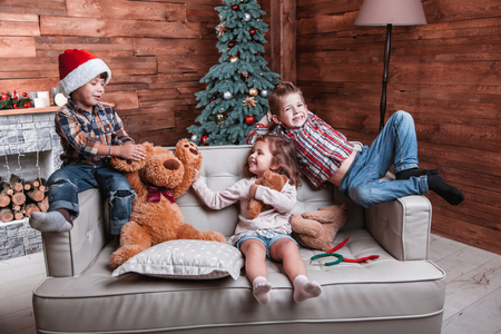 Beautiful happy laughing children playing on the sofa in a Christmas interior with Christmas tree and fireplace. The concept of a family holiday Reklamní fotografie