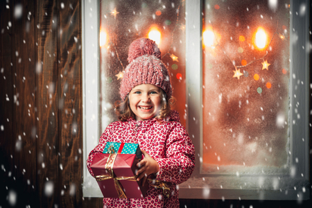 On Christmas night an adorable little girl near the window the snow falls. Reklamní fotografie