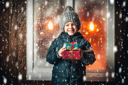 On Christmas night an adorable little boy with gift in hands near the window, the snow falls.