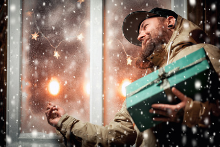 Christmas night, snow falling, funny man with a beard and with gifts in hands by the window. Winter background with lit garlands