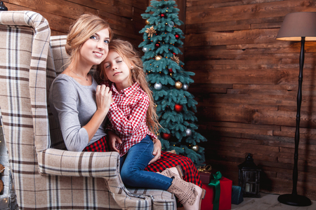 Beautiful happy mother with her daughter embrace in New Year interior with Christmas tree
