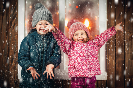 On Christmas night an adorable little boy  with his sister a girl play and laugh near the window the snow falls. They are waiting for Santa Claus.