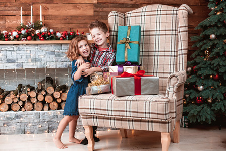 Beautiful happy laughing children in New Year interior with Christmas tree and fireplace. Brother hugging his sister. The concept of a family holiday