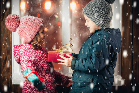 On Christmas night an adorable little boy  with his sister a girl with gifts in hand near the window the snow falls. They are waiting for Santa Claus.